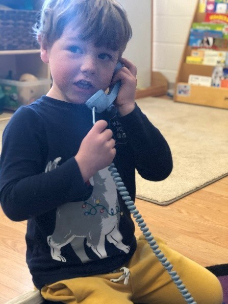 Young boy on a play phone in a classroom.