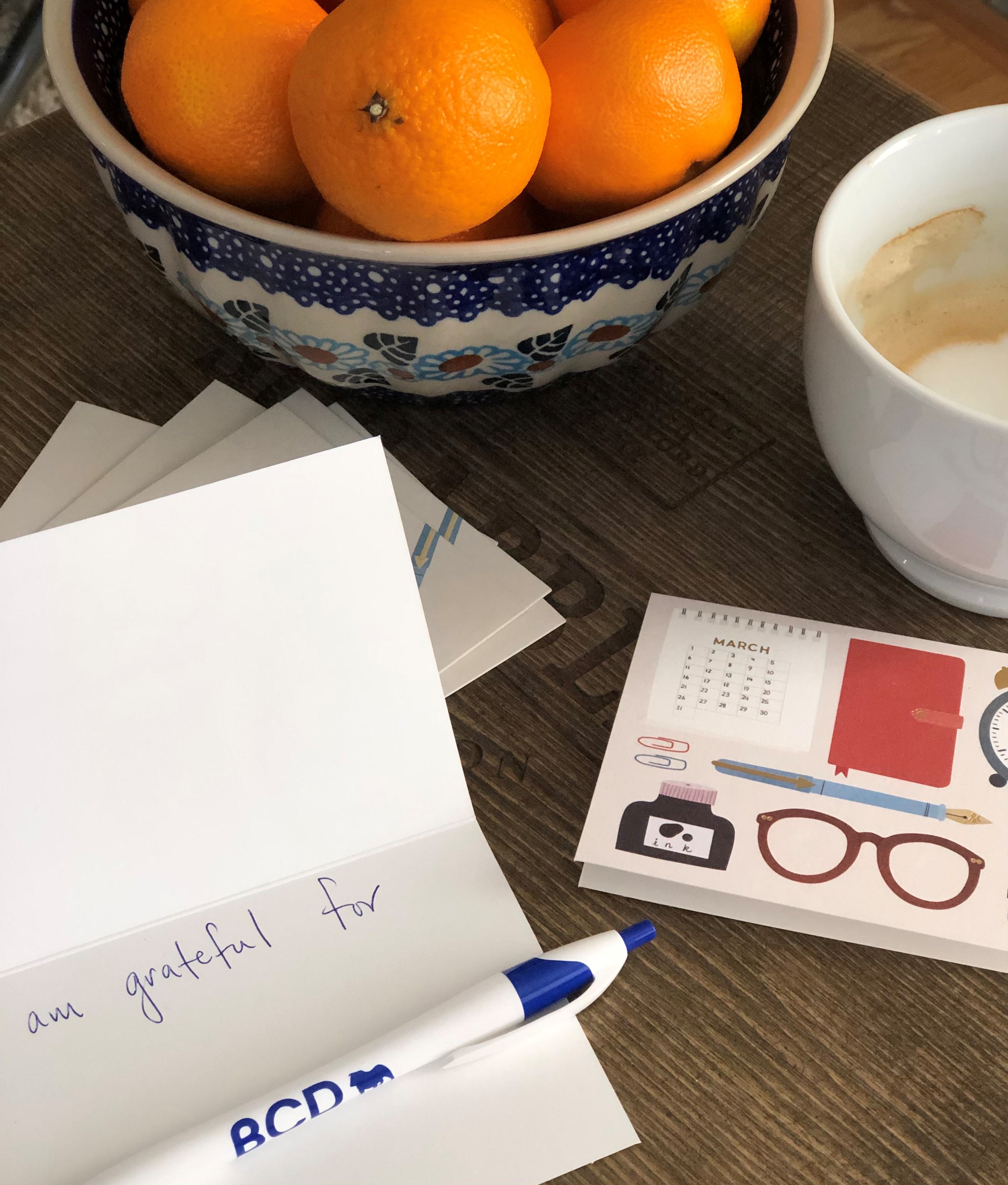 a table top with a bowl of fruit, a half drunk cup of coffee, a calendar, and a handwritten note starting with 'I am grateful for'