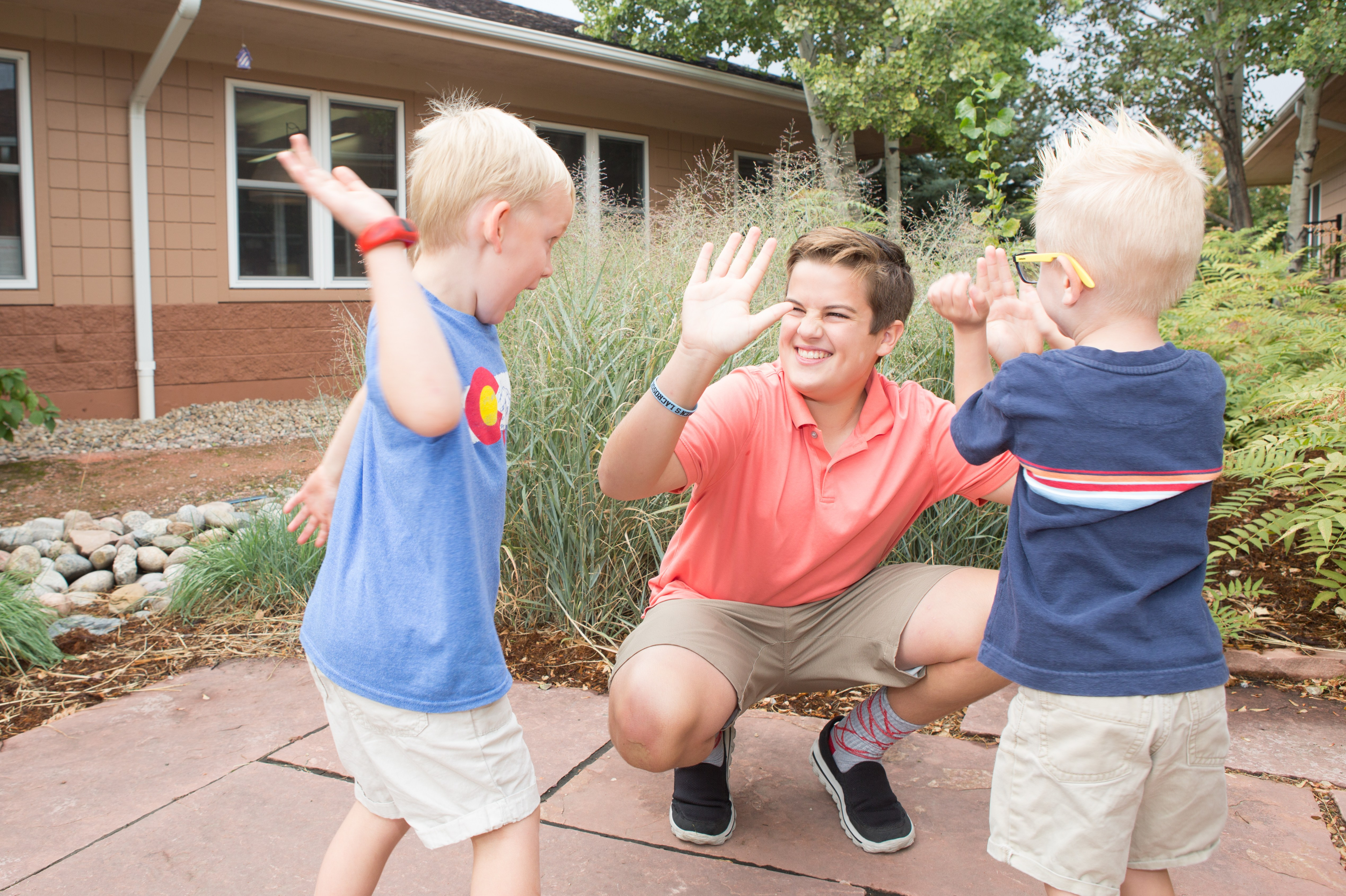 middle school boy is kneeling to give 2 preschool boys a high five