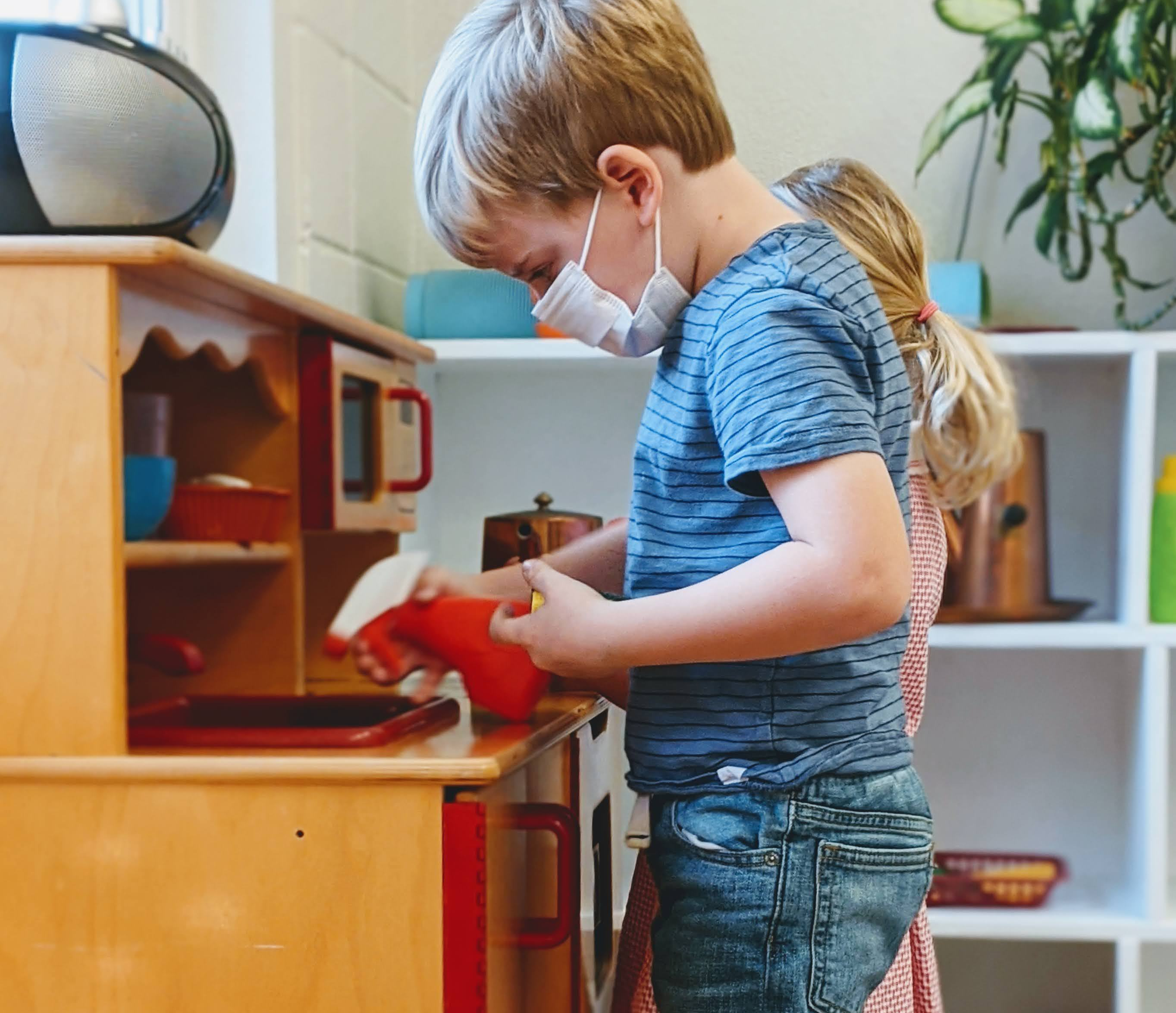 Child cleaning up pretend kitchen areas